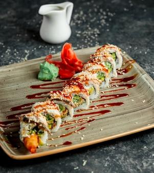 Um prato de rolo de sushi ebi servido com wasabi e gengibre