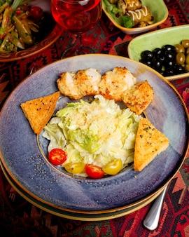 Um prato de salada caesar sem mistura com pedaços de frango frito