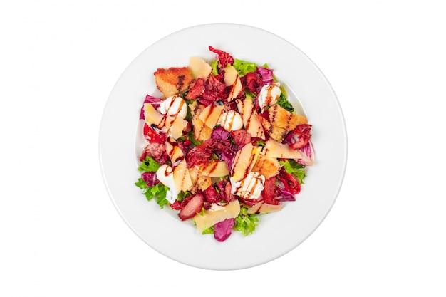 Um prato de salada com bacon, queijo de ovelha, tomate cereja