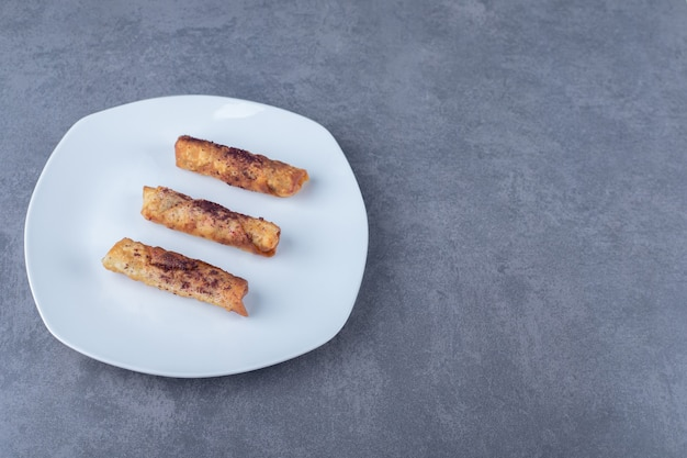 Um prato de sumagre sobre panquecas de carne na placa de madeira na mesa de mármore.