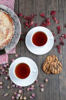 Um prato de torta deliciosa com chá preto colocado sobre uma mesa de madeira.