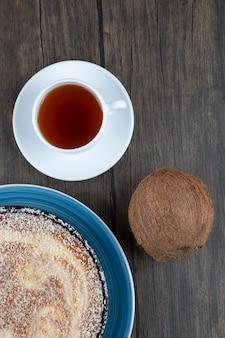 Um prato de torta deliciosa com coco fresco inteiro colocado sobre uma mesa de madeira.