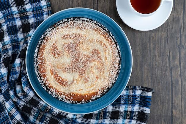 Um prato de torta deliciosa com uma xícara de chá preto colocado sobre uma mesa de madeira.