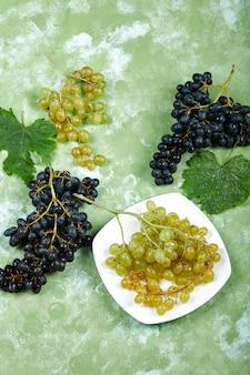 Um prato de uvas brancas e uvas pretas com folhas na superfície verde