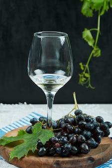 Um prato de uvas pretas com folhas e uma taça de vinho na superfície escura