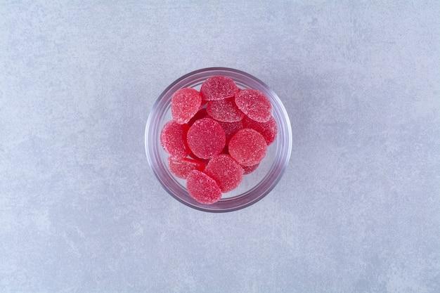 Um prato de vidro cheio de balas de geleia açucaradas na superfície cinza