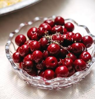 Um prato de vidro com cerejas