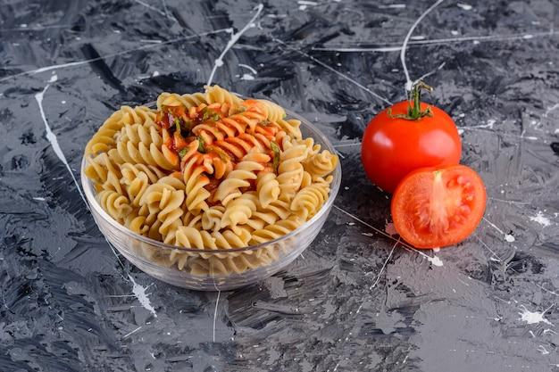 Um prato de vidro de macarrão fusilli multicolorido cru e seco com tomates vermelhos frescos