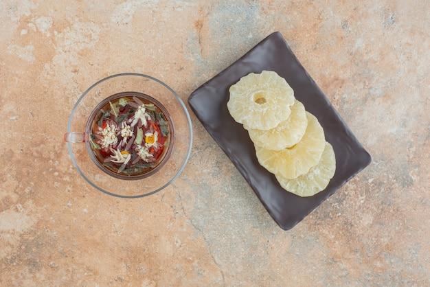 Um prato escuro cheio de abacaxi saudável seco e uma xícara de chá Foto gratuita