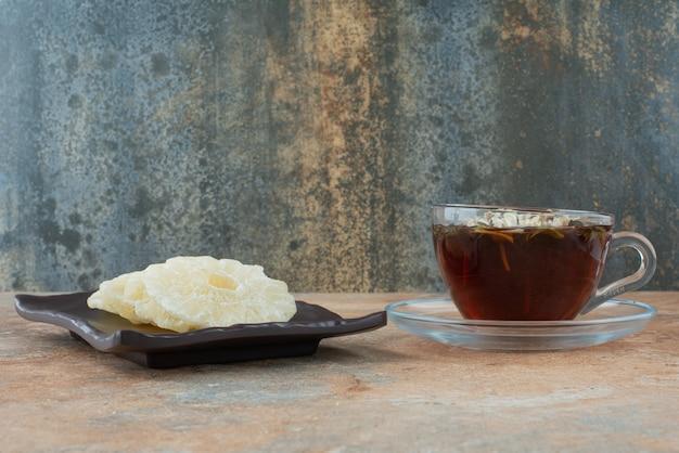 Um prato escuro cheio de abacaxi saudável seco e uma xícara de chá