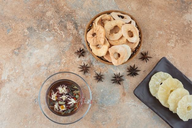 Um prato escuro cheio de abacaxi seco e uma xícara de chá de ervas