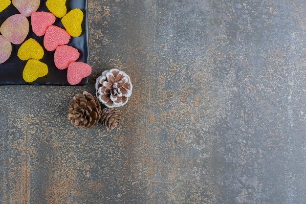 Um prato escuro cheio de balas de gelatina açucaradas em forma de coração com pinhas. foto de alta qualidade