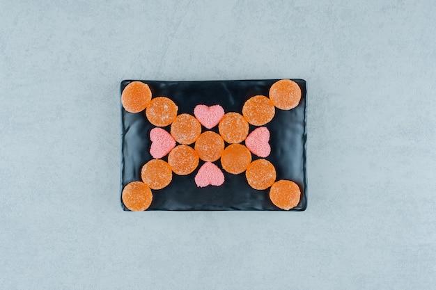 Um prato escuro cheio de balas de geleia de laranja doce com balas de geleia em forma de coração rosa