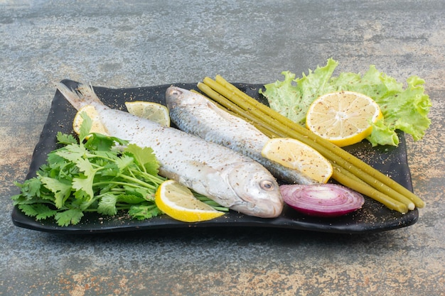 Um prato escuro cheio de peixes com limão e verduras sobre fundo de mármore. foto de alta qualidade