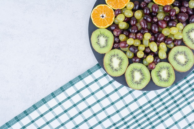 Um prato escuro cheio de uvas, kiwi e laranja na toalha de mesa.