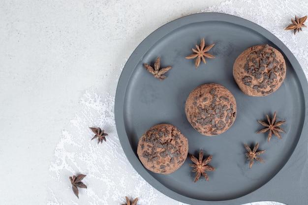 Um prato escuro com biscoitos de chocolate com anis estrelado.