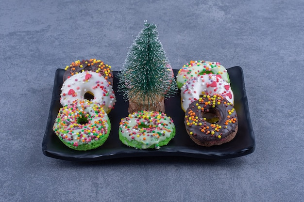 Um prato escuro com deliciosos donuts e uma pequena árvore de natal