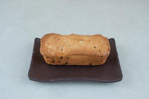 Um prato escuro com um delicioso bolo fresco na mesa branca.