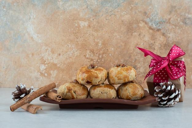 Um prato escuro de biscoitos com pequeno presente de natal e pinhas.