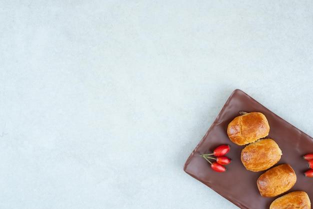 Um prato escuro de biscoitos doces e deliciosos com roseira brava.