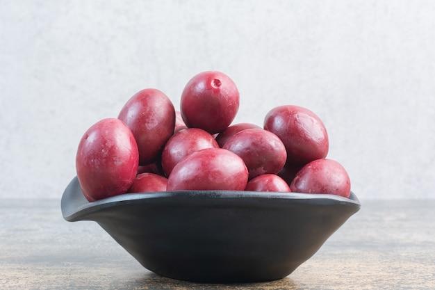 Um prato escuro de deliciosas frutas em fundo branco