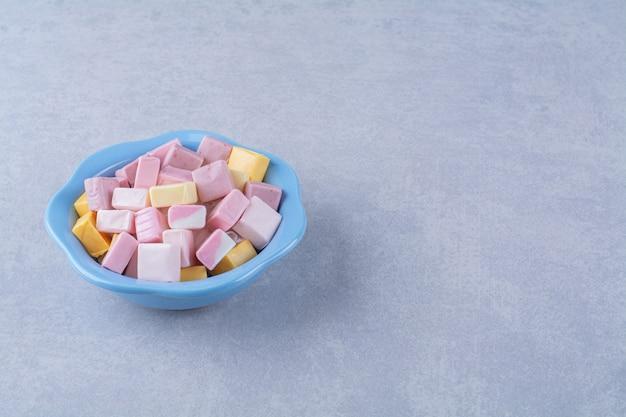 Um prato fundo azul cheio de doces pastéis coloridos pastila.