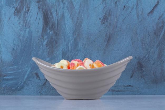 Um prato fundo cheio de doces de frutas coloridas.