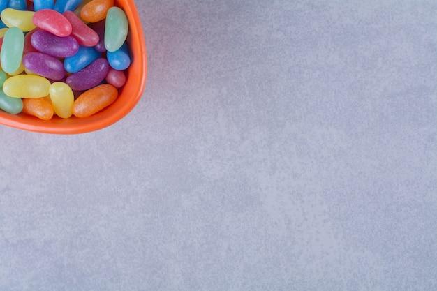 Um prato fundo laranja cheio de doces de feijão coloridos na superfície cinza