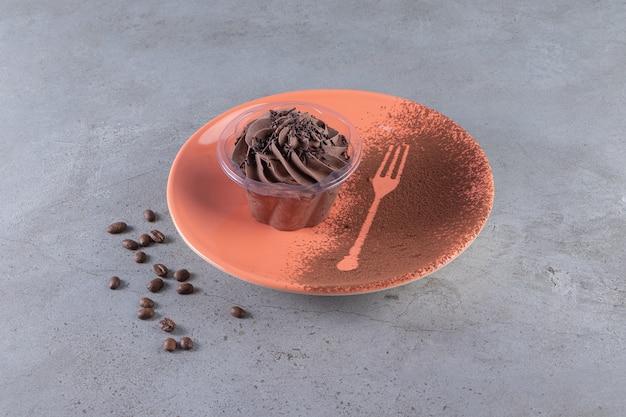 Um prato laranja com bolinho cremoso de chocolate e grãos de café.