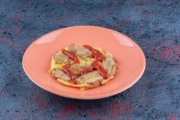 Um prato laranja com ovo frito e carne.