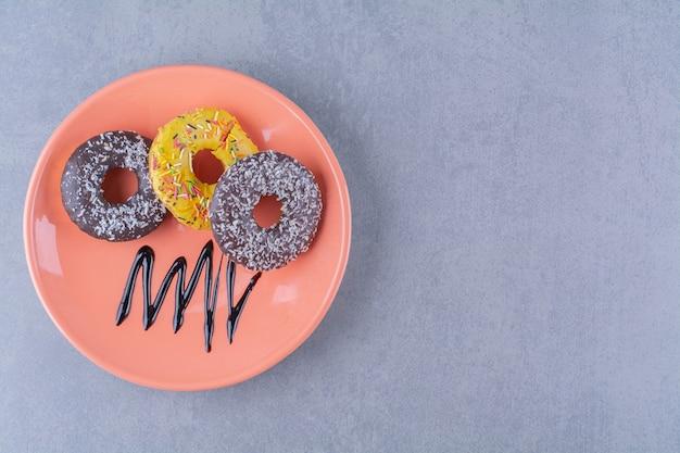 Um prato laranja de deliciosos donuts de chocolate com granulado.