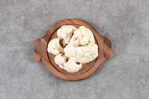 Um prato marrom cheio de couve-flor fresca e madura cortada em pequenos pedaços.
