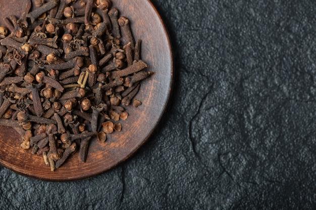Um prato marrom cheio de cravos-da-índia secos em um fundo escuro.