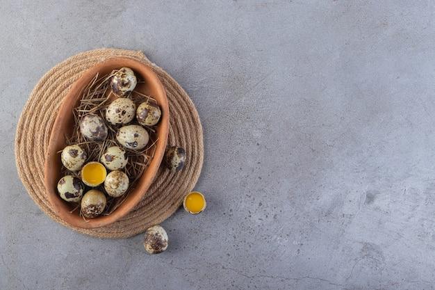 Um prato marrom cheio de ovos de codorna crus colocados na mesa de pedra.