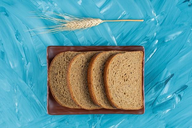 Um prato marrom com fatias de pão marrom e orelha na superfície azul