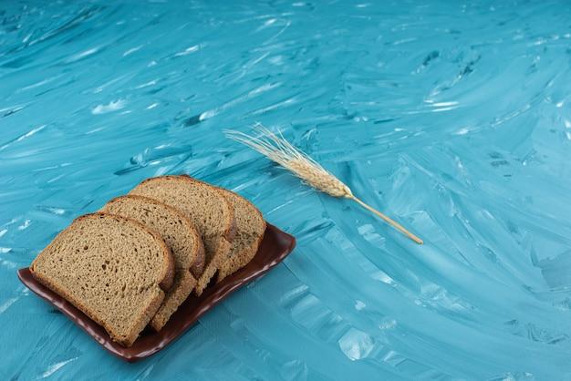 Um prato marrom com fatias de pão marrom e orelha sobre fundo azul.
