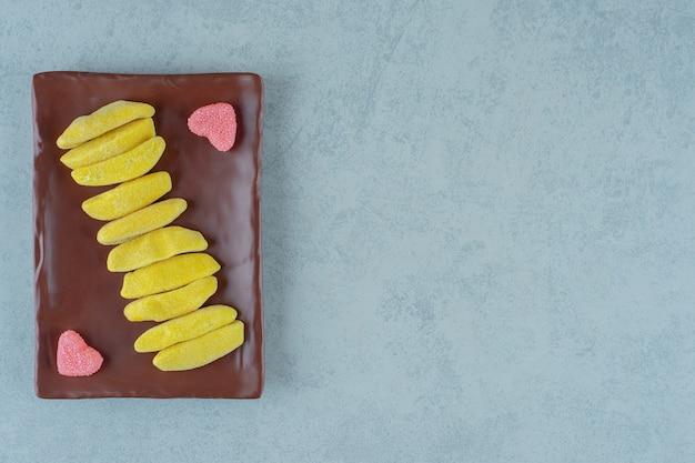 Um prato marrom de balas de mascar em forma de banana com balas de geleia açucaradas em forma de coração
