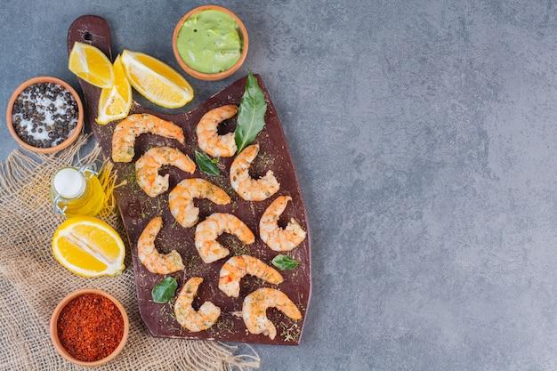 Um prato marrom de deliciosos camarões com fatias de limão e pimenta em um saco