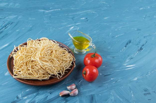 Um prato marrom de macarrão cru com dois tomates vermelhos frescos e óleo sobre um fundo azul.