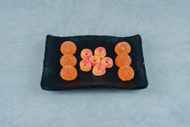 Um prato preto cheio de balas de geleia de laranja redondas em forma de anéis e balas de geleia de laranja com açúcar