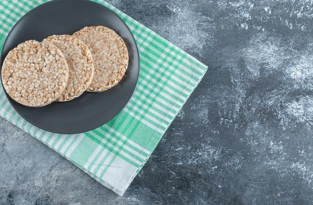 Um prato preto cheio de pão de arroz crocante sobre uma toalha de mesa.