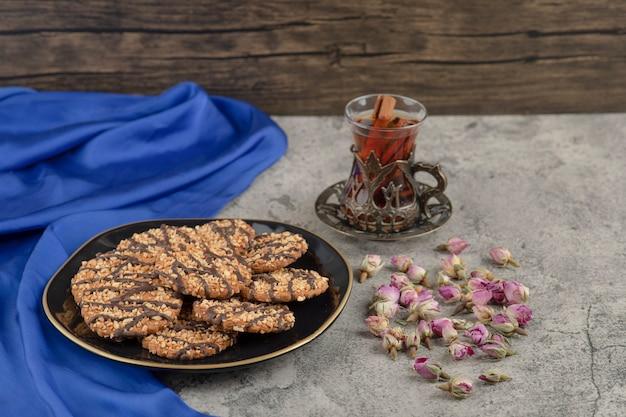 Um prato preto de biscoitos de aveia com uma xícara de chá e flores rosas murchas.