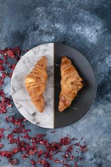 Um prato redondo com croissants frescos colocados sobre uma mesa de mármore.