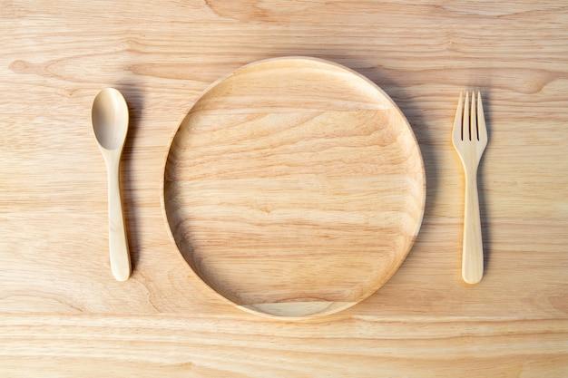 Um prato redondo e vazio, feito de madeira de borracha, com uma colher e um garfo colocados na placa de madeira, existe um espaço para copiar