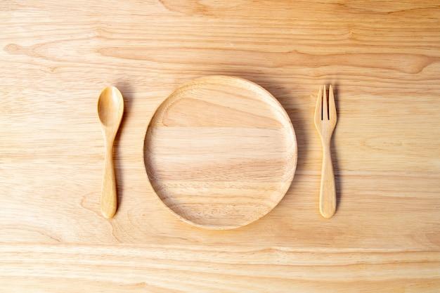 Um prato redondo feito de madeira de borracha e laca revestida com colheres e garfos e colocada em uma tábua de madeira no conceito de utensílio de cozinha.