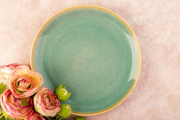 Um prato redondo verde com vista de cima e uma mesa de flores