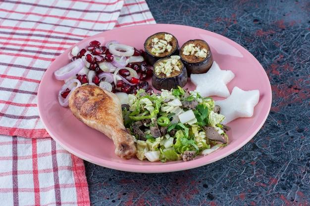 Um prato rosa de coxa de frango com legumes.