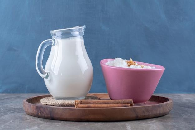 Um prato rosa de mingau de aveia saudável com uma jarra de vidro de leite e paus de canela em uma placa de madeira.