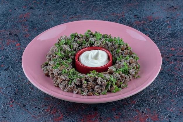 Um prato rosa de picadinho com ervilhas e ervas