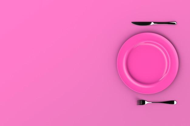 Um prato rosa vazio sobre uma mesa rosa e um garfo com uma faca. vista do topo